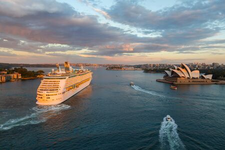 ocean liner: SYDNEY - MARCH 31: Large ocean liner unfolds in Sydney Harbour. View from the Harbour Bridge at sunset. March 31, 2016 in Sydney, Australia.
