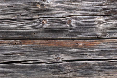 Wall of an old vintage wooden house built from hand-hewn pine logs. Colorful textured old wood cracked background