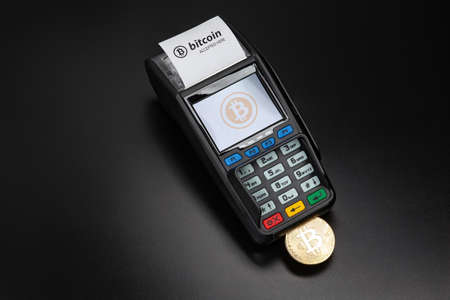Payment terminal ready to accept bitcoins for payment on the black background. Bitcoin gold coin sticks out of the POS terminal