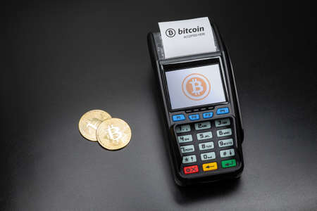 Payment terminal ready to accept bitcoins for payment. There are gold bitcoin coins on the black table nearby