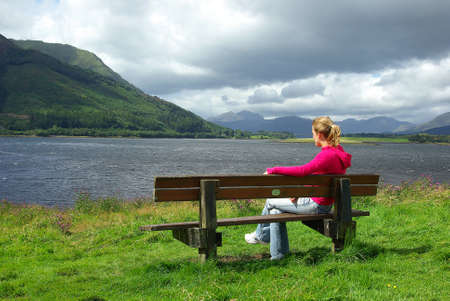 wind down: Yung woman meditating on a bench 2 Stock Photo