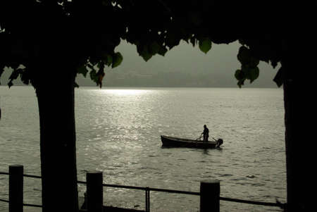 Fisherman on the Como lake in Italy at sunset photo