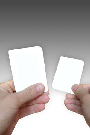 Photo of empty cards in hands on a grey background, to be personalised