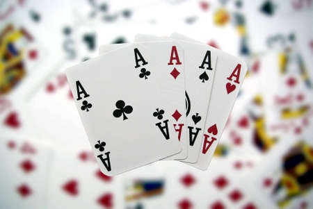 Poker cards showing a four-to-ace combination on a blurry background photo