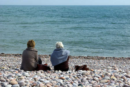 Senior ladies sitting on a pebble beach in Devon, with a view on the sea photo
