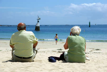Senior couple on the beach looking after their grandson.