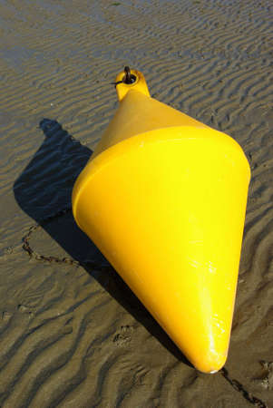demarcation: Delimitating sea buoy for navigation, on a beach in Brittany (low tide). Stock Photo