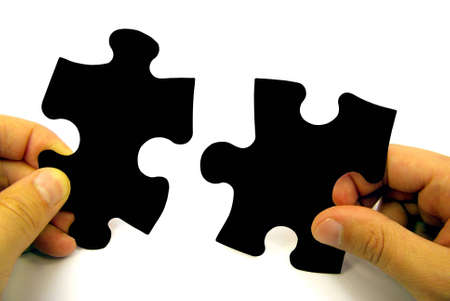 Human hands holding pieces of a puzzle over white background.