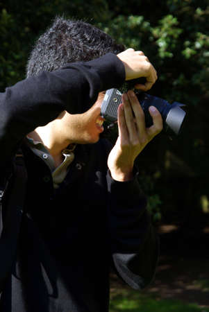 Profile view of a amateur photographer taking a photo. Stock Photo - 3802422