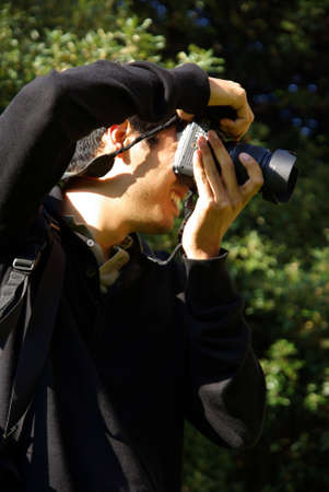 Profile view of a amateur photographer taking a photo. photo