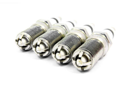 Detail view of an engine spark plugs over white background. Stock Photo