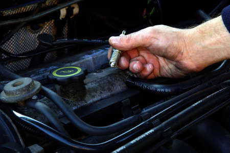 Man holding a spark plug in hand over a car engine.