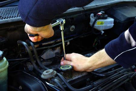 garage automobile: Homme tenant un outil pour travailler sur un moteur de voiture. Banque d'images