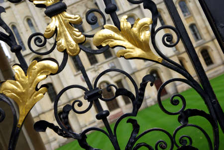 wrought: Ornamented fence detail in Oxford at the entrance of a college. Stock Photo