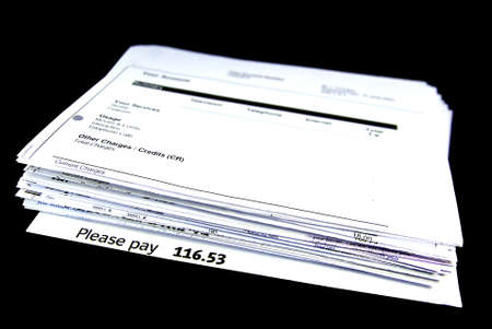 pay bills: Isolated stack of bills over a black background.