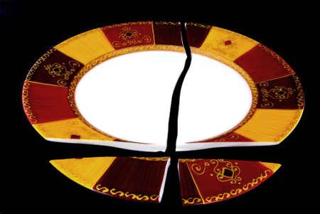 Broken plate over black background