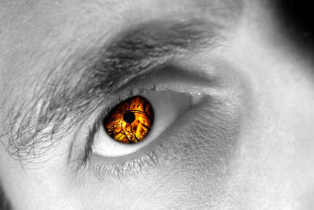 desire: Detail view of a male eye with flames instead of the iris. Stock Photo