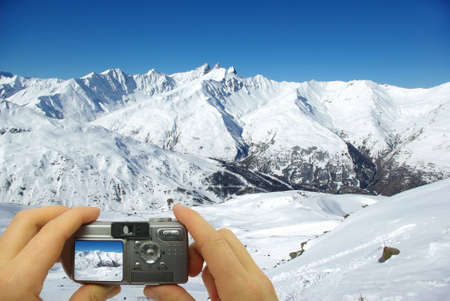 Photo montage of a tourist taking a photo of snowy mountains. photo