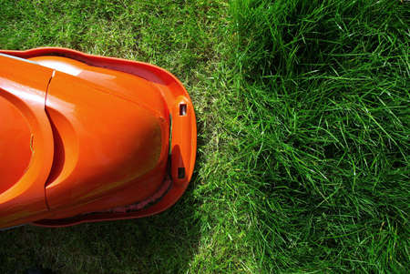 delimitation: Lawn mower at the limit of cut grass. Stock Photo