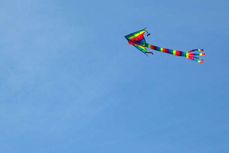 Striped colorful kite flying over a blue sky. photo
