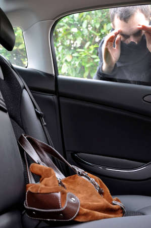 stealer: View of a burglar looking at a bag in a car.