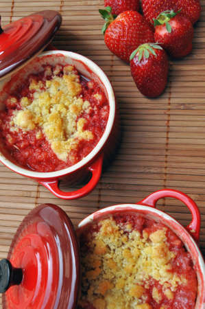 recipient: Close-up view on a strawberry crumble in ramekins. Stock Photo