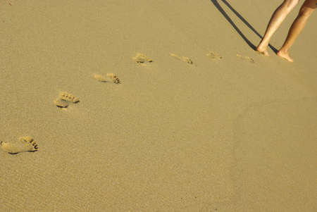 Image of lady fotprints in the sand.