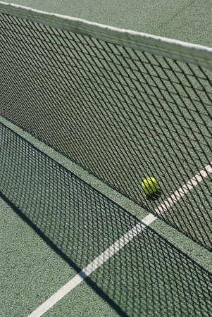 Tennis ball behind a net photo