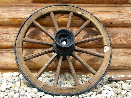 old wagon wheel side by wooden wall photo