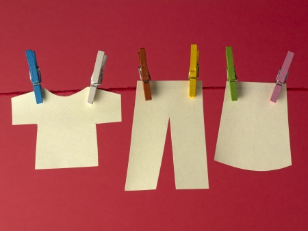 clothes peg: Sticky yellow papers notes hanging on clothes peg, on a red background  Stock Photo