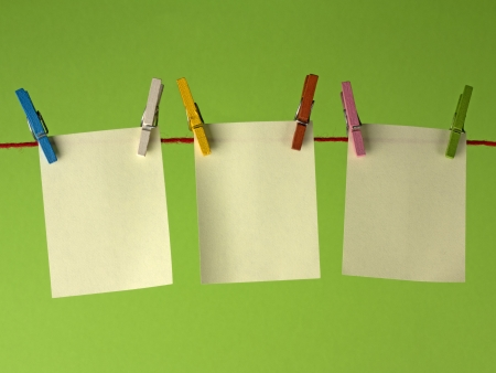 clothes peg: Sticky yellow papers notes hanging on clothes peg, on a green background