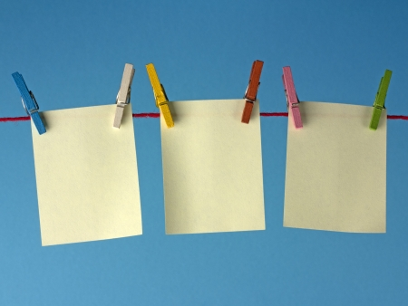clothes peg: Sticky yellow papers notes hanging on clothes peg, on a blue background