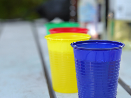 crucible: Disposable colorful cups with beverages on an outdoor party.