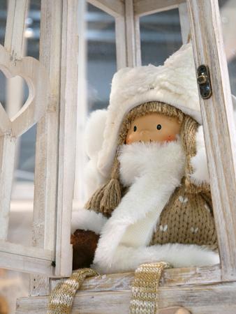 Muñeca de Navidad sentado en la lámpara decorativa