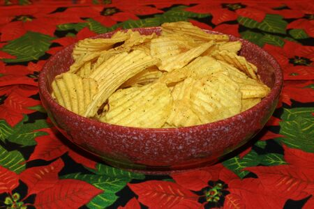 Heap chips in red spotted dish on a floral tablecloth. Stock Photo