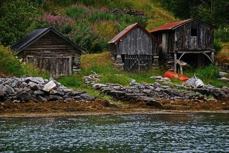 Tree old boat houses in Geiranger, Norway photo