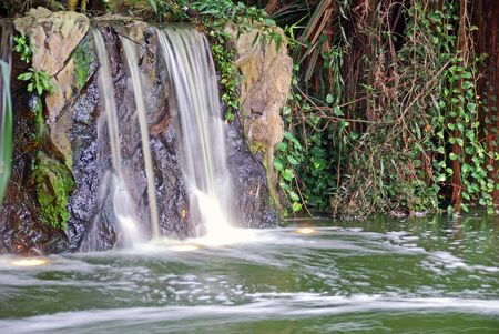 Small waterfall flowing into a small lake  photo