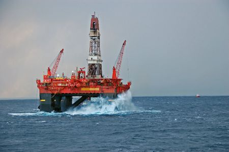Big waves hitting Oil platform in the North Sea Stock Photo
