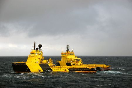 blue vessels: Anchor handling of an Semi Submersible Oil Rig in the North Sea. Stock Photo