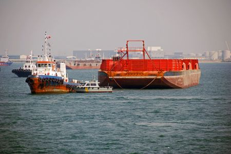 Small tugs handling a large barge at Singapore anchorage. Stock Photo