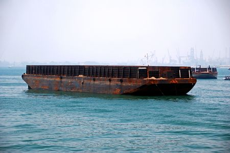 Large flat-bottomed barge towed by tug boat in Singapore anchorage. photo