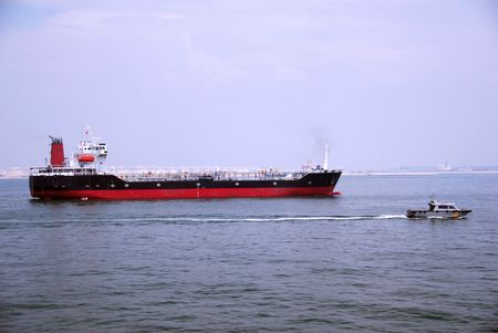 Small tanker (bunker) vessel passing Singaporean anchorage. Stock Photo
