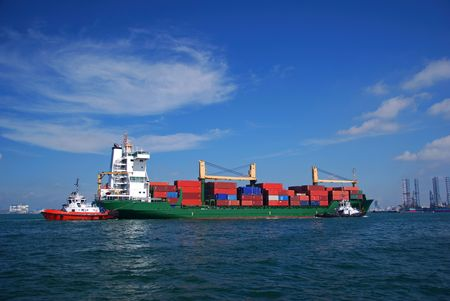 pilotage: Container vessel seen entering through Singapore anchorage. Stock Photo