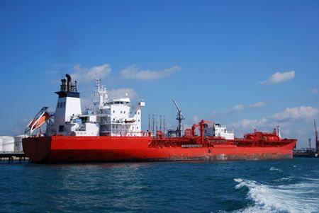 Orange chemical tanker seen moored at a terminal in Singapore. Stock Photo