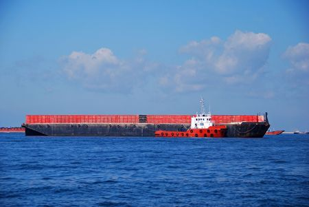 Tug boat towing a barge. Location is Singapore anchorage. photo
