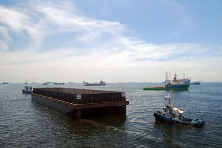 barge: Two tug boats towing a barge. Location is Singapore anchorage.