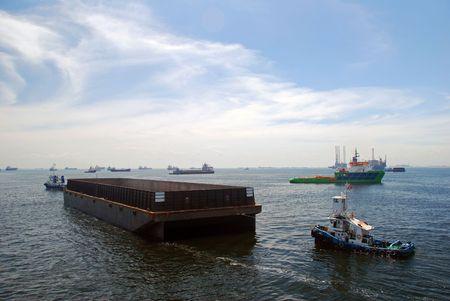 Zwei Zug-Boote ein Lastkahn schleppen. Speicherort ist Singapur Ankerplatz.