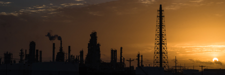 Silhouette oil refinery at sunrise. Oil factory, petrochemical plant tower, gas flare, smoke stacks and machinery in Corpus Christi, Texas, USA. Petroleum industry background. Panorama style.