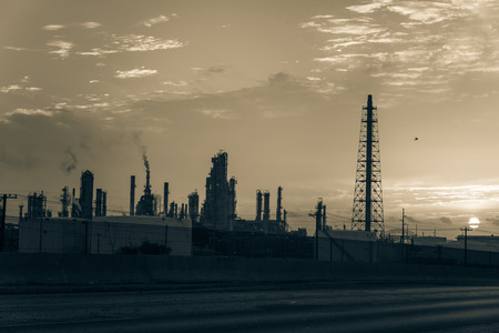 Silhouette oil refinery at sunrise. Oil factory, petrochemical plant tower, gas flare, smoke stacks and machinery in Corpus Christi, Texas, USA. Petroleum industry background. Vintage tone. Stock Photo