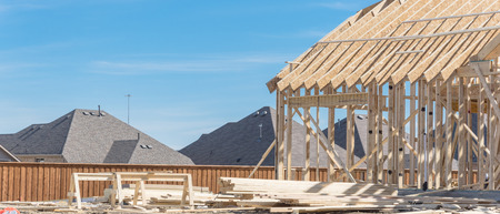 Hilltop wood frame house under construction near completed homes in Irving, Texas, USA. New two-story stick built, joist, timber frame panels and temporary struts. Pile of logs, plank, beam. Panorama